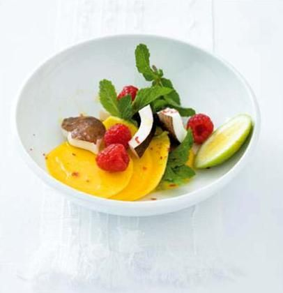 Mango, coconut and raspberry salad with pink peppercorns and mint leaves