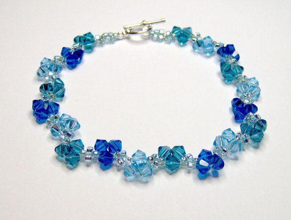 Un bracelet délicat à l'aide de toupies swarovski dans différentes nuances de bleu. Les couleurs utilisées sont capri bleu, aquamarine et indicolite, également utilisé sont des perles de rocaille AB aqua clair et terminé par un fermoir en t plaqué argent. Longueur du bracelet, fermoir compris est de 19 cm (7,5 pouces) qui convient pour un poignet de 5.5-6 pouces et la largeur est de 1 cm (0,4 po). S'il vous plaît vérifier la taille du poignet avec soin avant d'acheter. Bracelet sera dans…