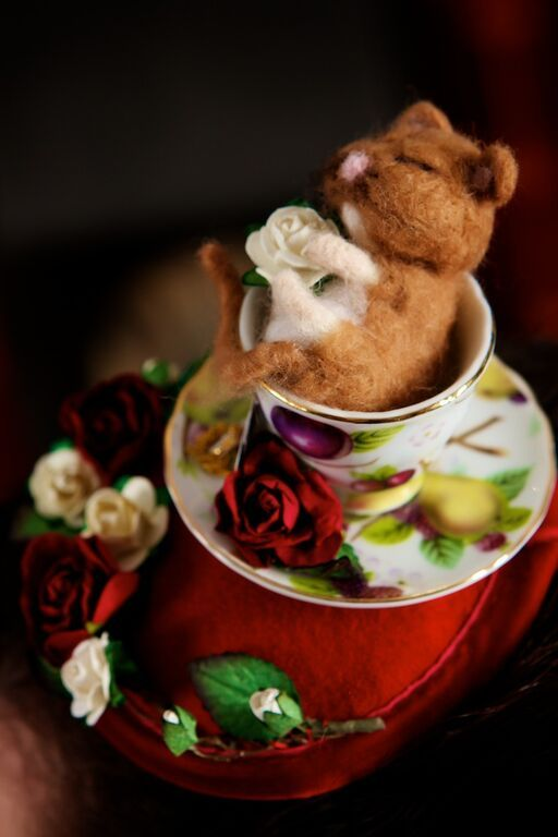 Alice in Wonderland Fascinator featuring red and white mulberry paper roses and a sleeping needlefelted dormouse in a wee china teacup.