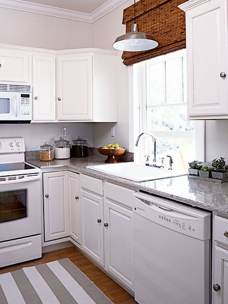 White kitchen appliances disappear against coordinating white cabinets. Classic granite countertops reinforce the simple, but classic style of this coastal kitchen. The fabric-lined bamboo Roman shades filter the late-afternoon sun.