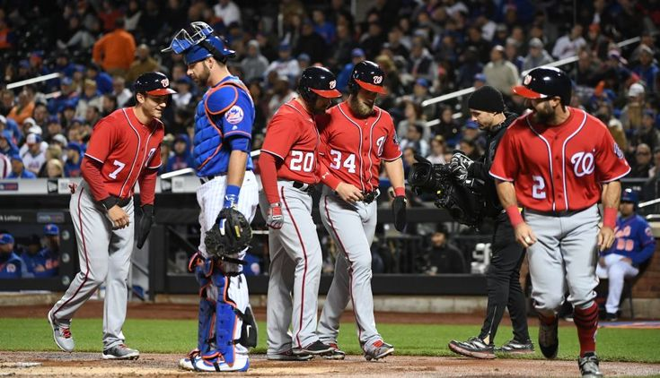 Washington Nationals second baseman Daniel Murphy (20) is met at home plate by Trea Turner, Bryce Harper and Adam Eaton after his grand slam as New York Mets catcher Kevin Plawecki looks on during the first inning in an MLB baseball game at Citi Field on Sunday, April 23, 2017.