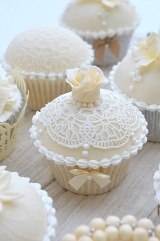 Vintage-themed white wedding cupcake with lace, roses, bows, and pearls #wedding #vintage #cupcakes #weddingcupcakes #white