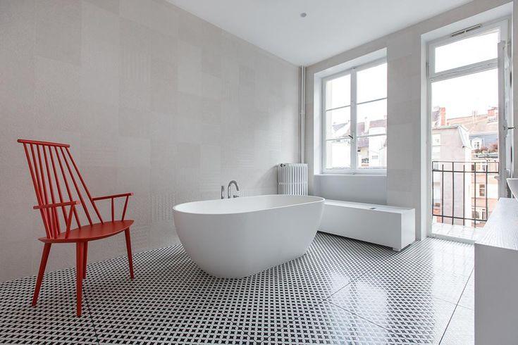 REINVENTARE IL CLASSICO A STRASBURGO: IL BAGNO Il bagno è stato trasformato in una grande stanza luminosa con una vasca da bagno freestanding, una seduta J110 di Hay rossa e un doppio affaccio sul balcone che dà sul cortile interno.