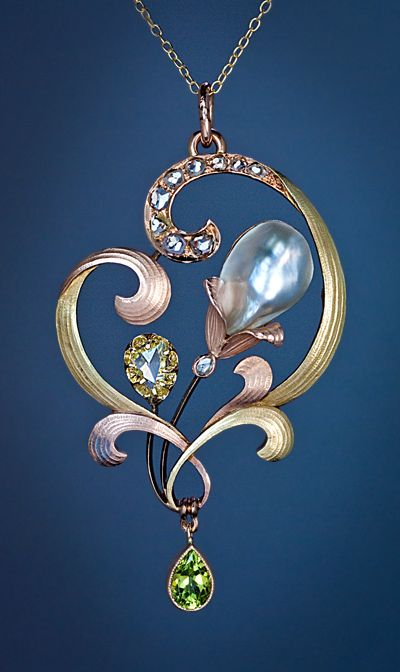 An Elegant Art Nouveau Jeweled Gold Pendant Made in the city of Odessa between 1899 and 1908. An openwork rose, green and yellow gold pendant is designed as a stylized flower in Art Nouveau taste. The pendant features a large (14 mm wide) baroque pearl, a triangular shaped rose cut diamond, a drop shaped peridot and nine old mine and rose cut diamonds | JV
