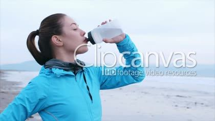 Slow motion video of fit woman drinking water on beach. Sporty female is in blue jacket. She is looking away while watching waves crashing. HD Stock Footage Clip. Medium shot. 2016-01-15.