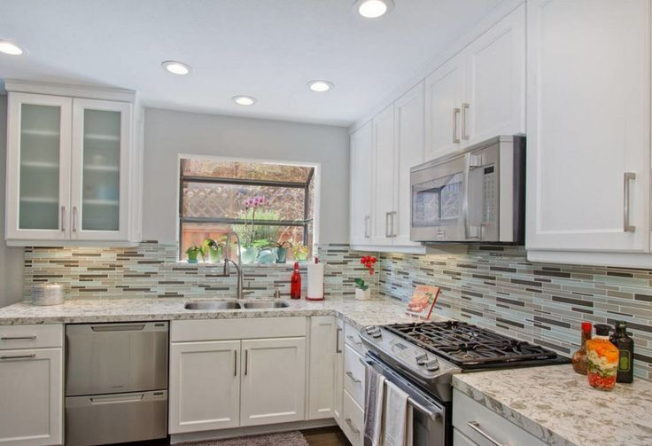A magnificent design by DSO Designs this bright, airy open-concept space features PentalQuartz countertops in Serra and glass tile backsplash!