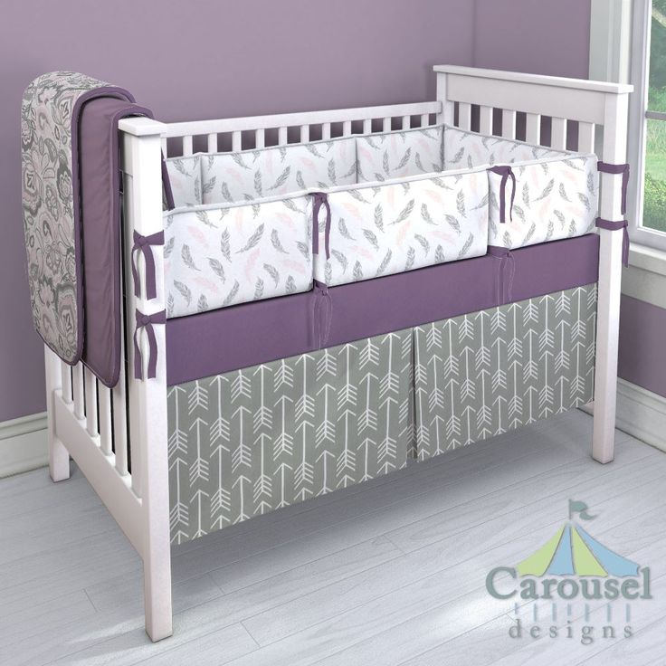 Crib bedding in Solid Violet, Pink and Gray Jacobean, Solid Aubergine Purple, Gray Arrow, Blush Pink and Silver Gray Hand Drawn Feathers. Created using the Nursery Designer® by Carousel Designs where you mix and match from hundreds of fabrics to create your own unique baby bedding. #carouseldesigns