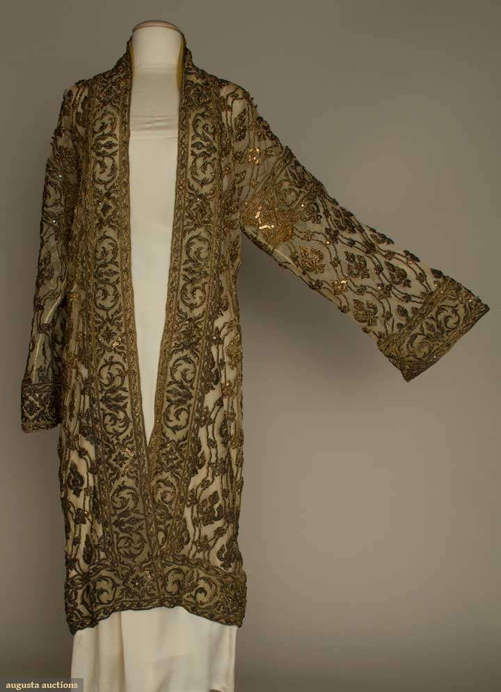 "Gold embroidered Evening coat, Heavy cotton net, embroidered in metallic gold buillion & thread forming raised stylized lilies w/in horizontal wavy bands, Ch 40"", L 46"", (repairable tear under L arm, embroidery tarnished) very good. Brooklyn Museum"