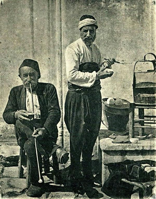 a 'kahveci' (coffee seller) and a smoking costumer. Istanbul, early 20th century.