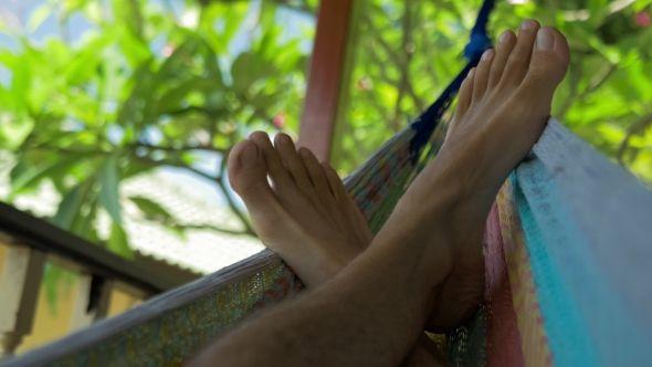 Swinging Bare Man Feets in a Hammock on Terrace. Vacation on Koh Tao Tanote Bay, Thailand