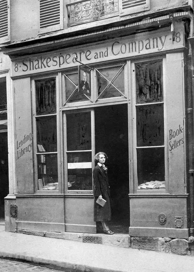 """American publisher Sylvia Beach stands in the doorway of her bookshop """"Shakespeare & Company"""", during the 1920s."""
