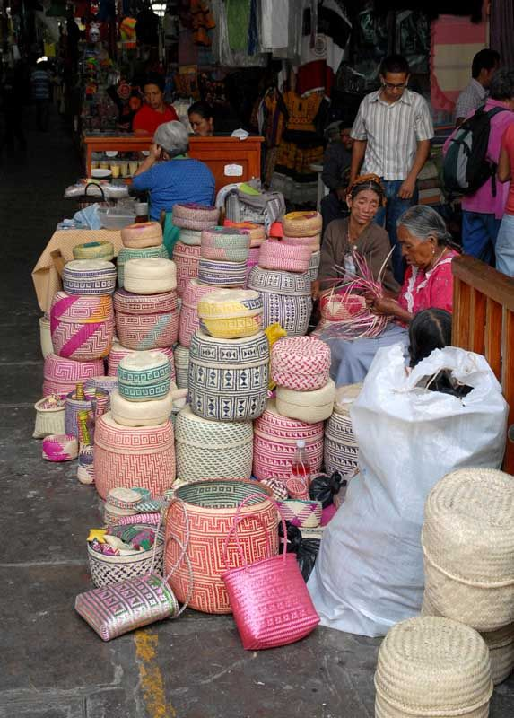 Basket Makers Oaxaca The women weaving these plaited palm baskets are from the Zapotec community of San Luis Amatlan, a small town near Miahuatlan, Oaxaca Mexico. They weave and sell their baskets at one of the entrances to the Benito Juarez market in Oaxaca. Plaited baskets are also woven by Mixtec women in the Tlaxiaco area of the Mixteca Alta.
