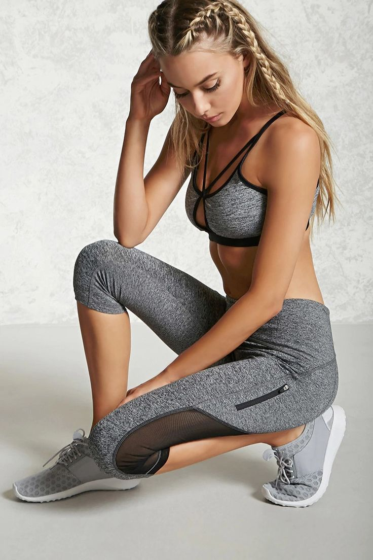 A pair of knit athletic capri leggings featuring sheer mesh panels, a hidden key pocket, front zippered pocket, and moisture management.