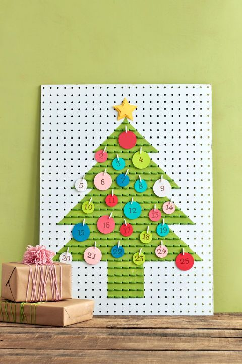 "This twist on the Advent calendar features a daily idea for getting into the spirit. Step 1: Draw outline of a tree on a pegboard. (Ours measures 24"" W × 32"" H.) Mark off outline with painter's tape. Paint tree green. Step 2: Stitch green yarn through holes of painted tree, using a basic backstitch. Knot in back to secure. Step 3: Use round paper punches to create 25 circles of colored paper. Step 4: Stamp numbers 1 through 25 on the circles, then jot a holiday activity on opposite side…"