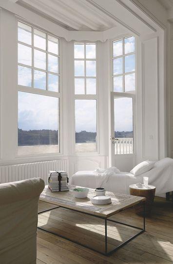Salon tout de blanc vêtu dans le bow-window face à la mer - Déco chic en Bretagne - CôtéMaison.fr