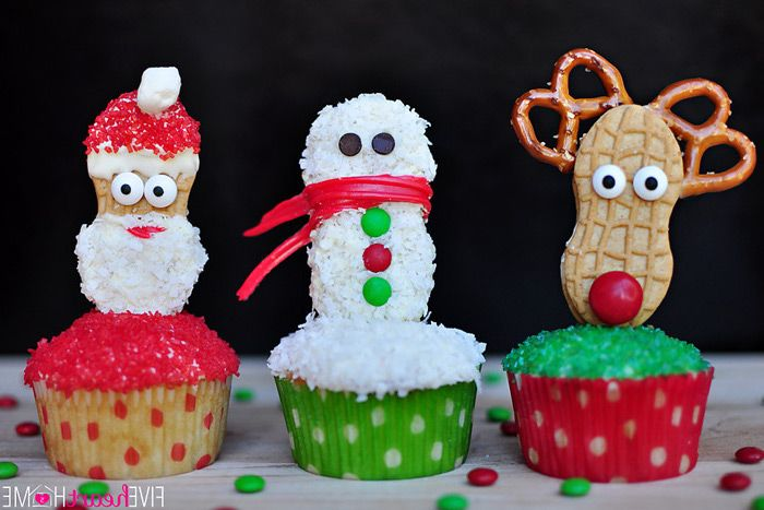 three cupcakes with red, white and green sparkling sugary frosting, decorated with cookies made to look like santa, snowman and rudolph
