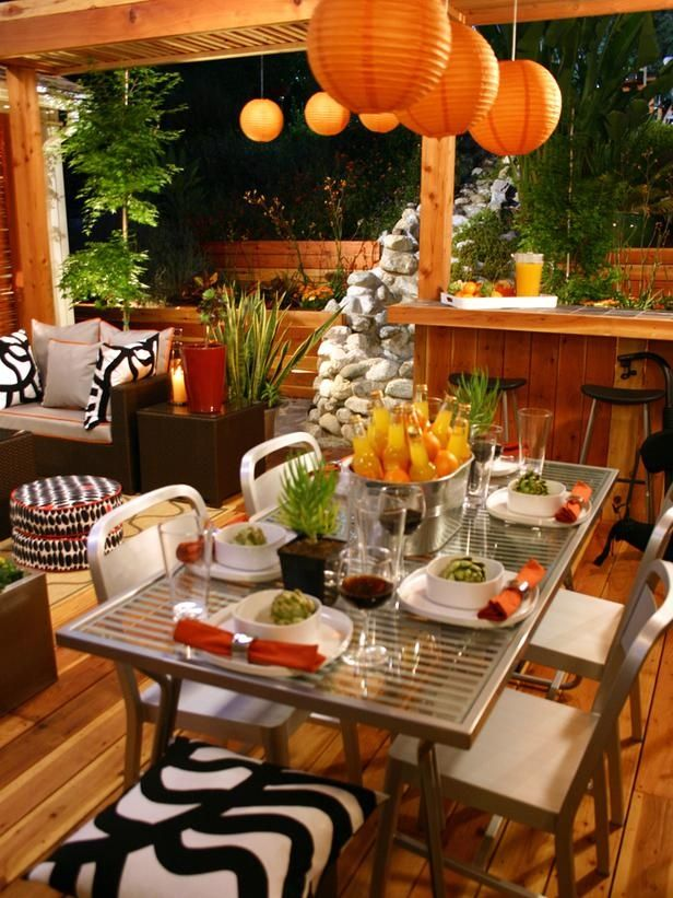 A rattan sofa and an aluminum dining table make a cozy, sleek outdoor party space.