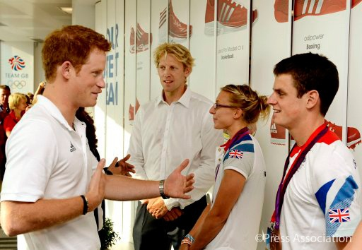 Prince Harry talks to Bronze medal winning triathlete Jonathan Brownlee (right) at Team GB House in the Westfield Centre, Stratford, east London.