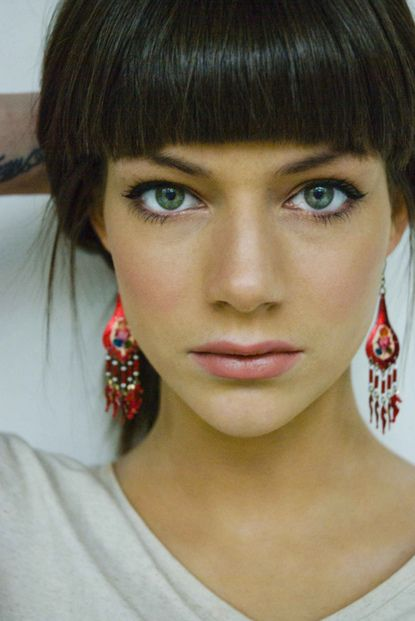 this woman mesmerized me. Love the clean and simple look. Striking eyes. Add the bangs and the tattoo. Oh dear.