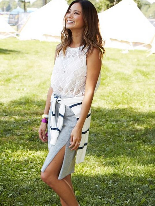 Jaime Chung wears a mesh grid white tank top, grey skirt with a thigh slit, and a striped sweater tied around the waist.