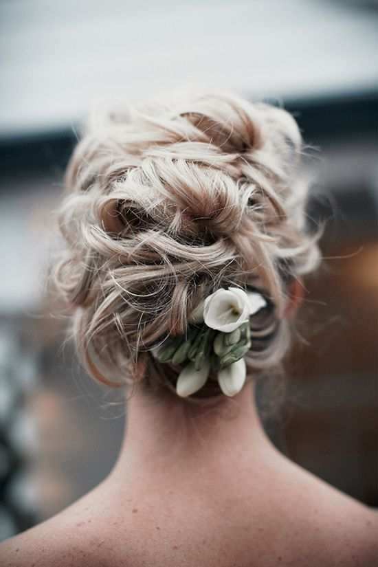 Beautiful messy style updo . Love the fresh flower!