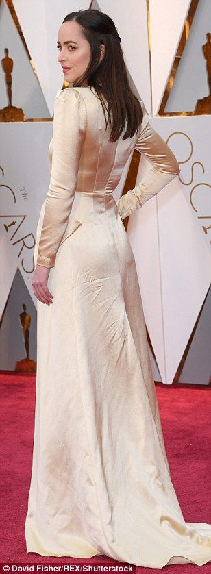 Golden girl: Dakota Johnson glimmered in her golden Gucci creation...