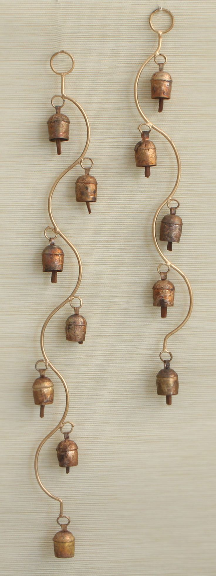 Bring music to your surroundings with this long and curving wind chime hand crafted by artisans in India.