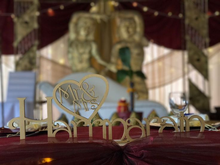 Monte Vista Venue custom Mr and Mrs sign on the main table in front of the stage at a gold and maroon Hindu wedding.