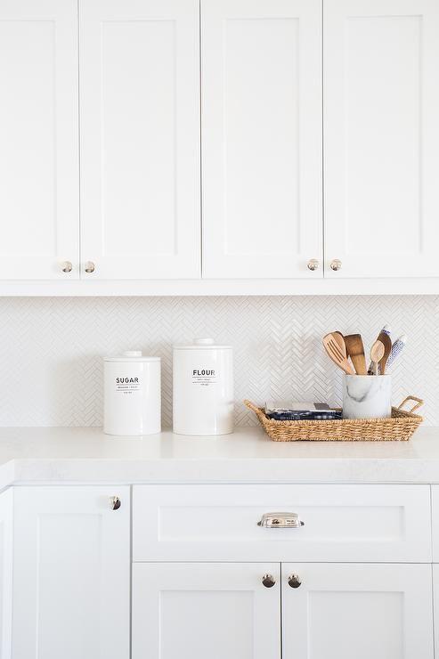 Lovely white kitchen features white shaker cabinets paired with a white marble like quartz countertops, Caesarstone Calacatta Nuvo, and a white mini herringbone tiled backsplash, Ann Sacks Savoy Mosaics Herringbone Tile in Ricepaper.
