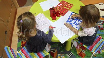 Girls drawing at the table - preschool to kindergarten during educational activities.