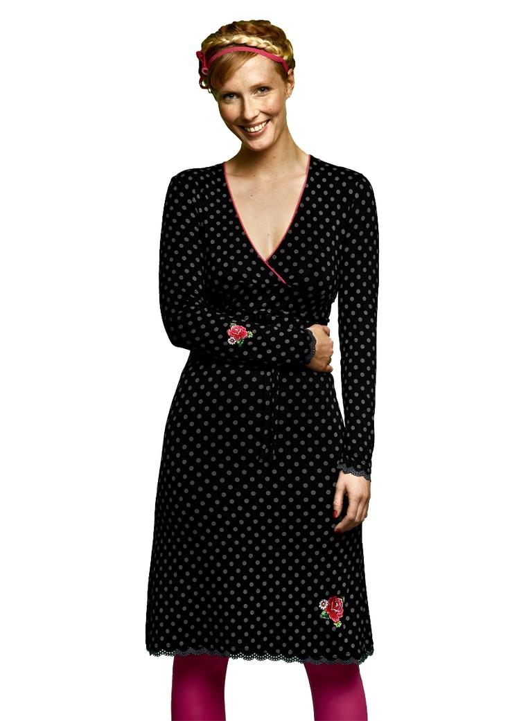 Overslag jurkje van een zwarte met grijze polka dot tricot. heerlijk soepel vallend. Met een bindlintje in de taille en een rozenborduursel op het rokgedeelte,  en op het mouwtje ,langs de hals een klein fuchia kleurig kantje.  Zeer veelzijdig te dragen, chique met een panty en pumps, casual met een legging en laarzen. De lengte van van de jurk bij maat S is 100 cm.    95% viscose 5% elastan    Binnenstebuiten wassen op 30 graden met een fijnwasmiddel, niet in de droger.