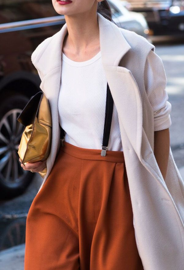 Suspenders and rust coloured pants with a white tank top and blush pink coat plus gold clutch