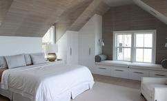 Modern landelijke slaapkamer op zolder. Leuke zitplek met opbergruimte bij het raam.
