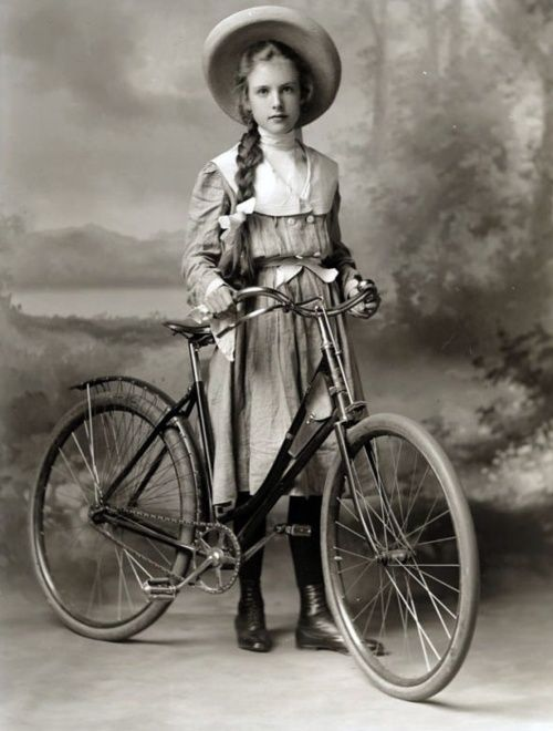 A girl stands with her treasured bicycle before a painted photography backdrop.