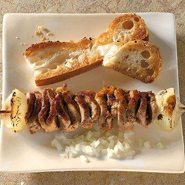 Kroatischer Schnitzelbraten 1 kg Schweinelende am Stück, 350 g Zwiebeln, 3 Knoblauchzehen, 3 EL Öl, 1 EL Paprikapulver, edelsüß, 1 TL Paprikapulver, rosenscharf, 1 EL getrockneter Majoran, Salz, Pfeffer, Grillspieß, Öl für den Spieß und den Rost