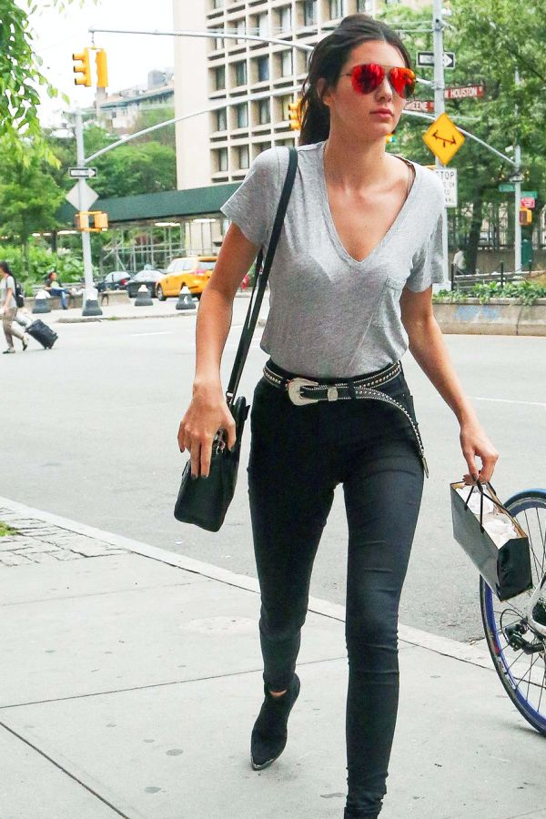 Kendall Jenner in a grey tee, skinnies, and a western style belt