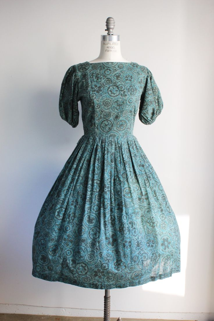 Absolutely gorgeous 1950s batik print dress in greens and teals. Metal zipper up the back, full pleated skirt. Interesting squared off neckline, and short sleeves that are gathered with elastic at the
