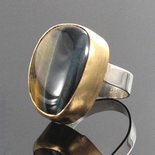 Okazały pierścień z niebanalnym kamieniem - sokole oko w pięknych granatowo-złotych barwach. Oprawa kamienia zmatowiona i pozłocona, obrączka wykończona na wysoki połysk. Dla miłośniczki okazałej efektownej biżuterii. Wymiary kamienia 27x21mm, szerokość obrączki 5mm. Rozmiar jubilerski 17-18, nie ma możliwości dopasowania do innego rozmiaru, ale na zamówienie można wykonać podobny pierścionek pod konkretny rozmiar. Praca sygnowana, zapakowana w eleganckim firmowym pudełku.