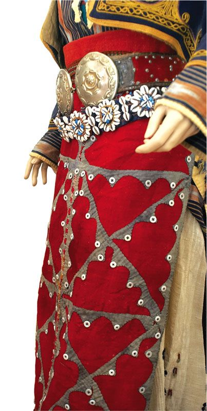 A 'önlük' (apron) and two belts: one with metal buckle, one with 'göz' motif (amulet) in seashells and coloured pearls.  Parts of a traditional bridal costume from Merkez Kapıkaya köyü (near Bergama, north of Izmir).   Mid-20th century.  Ethnic group: Alevi Türkmen.
