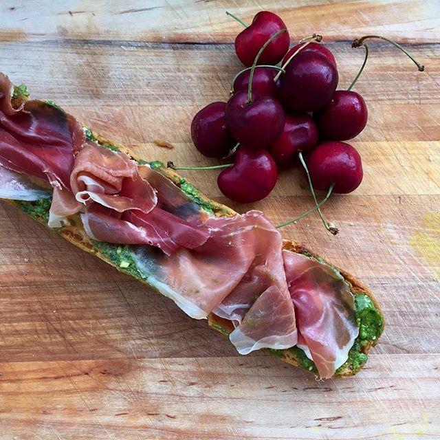 Open faced sandwich of prosciutto, homemade arugula & basil pesto and soft goat cheese 🌿🍒💚