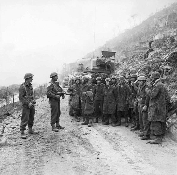 German prisoners captured by New Zealand troops are held at gunpoint on a road beside a Sherman tank outside Cassino, Italy, March 1944.