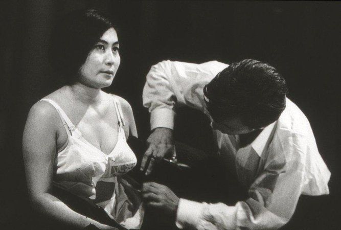 Ono. Another Fluxus artist, Yoko Ono (b. 1933), created Cut Piece in 1964 (see above), in which she kneeled on a stage and invited audience members to cut off pieces of her clothing with scissors.