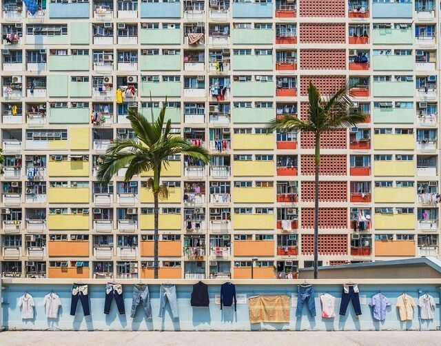 "DECEMBER 31, 2017RAINBOW VILLAGE  Laundry dries off the railings of Choi Hung estate, a housing complex in Hong Kong. The name means ""the Village of Rainbow"" in Cantonese, and the buildings house more than 40,000 people. The colorful apartments were built in the 1960s, and cover 11 city blocks.  PHOTOGRAPH BY HAITONG YU,"