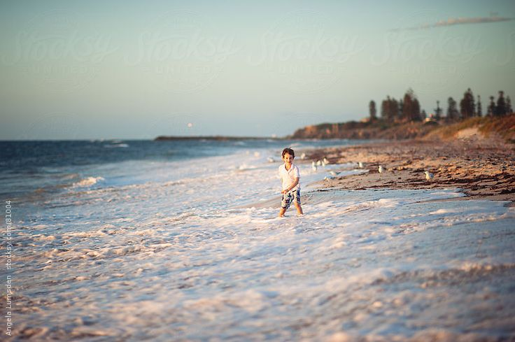 Boy playing in waves at the beach by Angela Lumsden