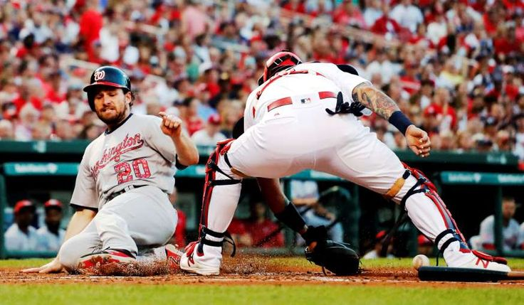 HE'S SAFE:    Daniel Murphy (20) of the Washington Nationals scores as the throw gets away from St. Louis Cardinals catcher Yadier Molina during the third inning July 2 in St. Louis. The Nationals won 7-2.