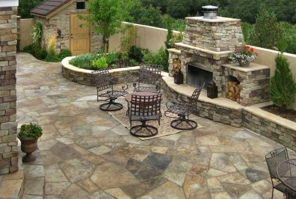 Love this flagstone patio and fireplace, raised planter beds, and cute storage shed