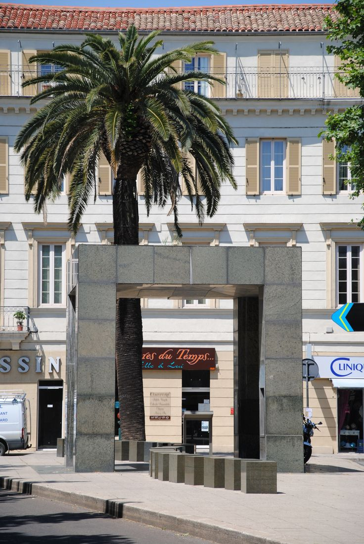 Abribus - Philippe Starck - Nîmes Réalisé en marbre sombre, cette création représente l'emblème de la Ville de Nîmes : le crocodile et le palmier.