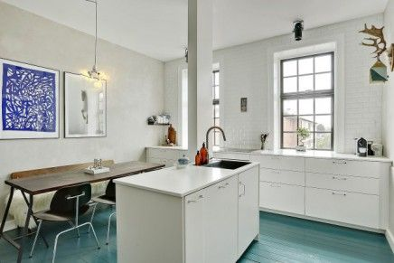 Door het gehele appartement ligt een mooie houten vloer zoals in de woonkamer. Bijna overal wit, behalve in de keuken. Daar is de houten vloer namelijk turquoise blauw geschilderd. Een gewaagde zeldzame kleur, maar eentje die hier bijzonder goed uitpakt. Vooral in combinatie met de lichte betonstuc muren, wit geschilderde bakstenen muur, strakke witte keuken met eiland en de vintage houten eettafel. Een droomkeuken!