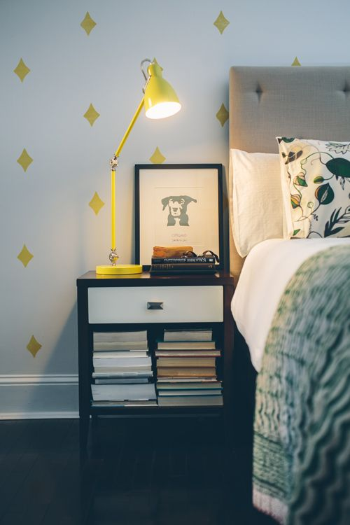 """Sneak Peek: Kiera Kushian. """"Our bedroom is one of my favorite rooms in our place. It took me forever to commit to a color scheme but we couldn't be happier with how the yellow and green accents always have us waking up happy! All of the walls in our place are Benjamin Moore Decorators White... After a few months living here we decided the room needed something else so we did a little DIY with a custom stamp and inkpad and added the yellow diamond stamps to just one wall."""" #sneakpeek"""