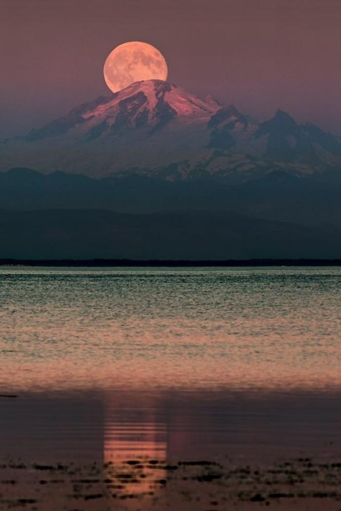la pleine lune aui se lève derrière la montagne